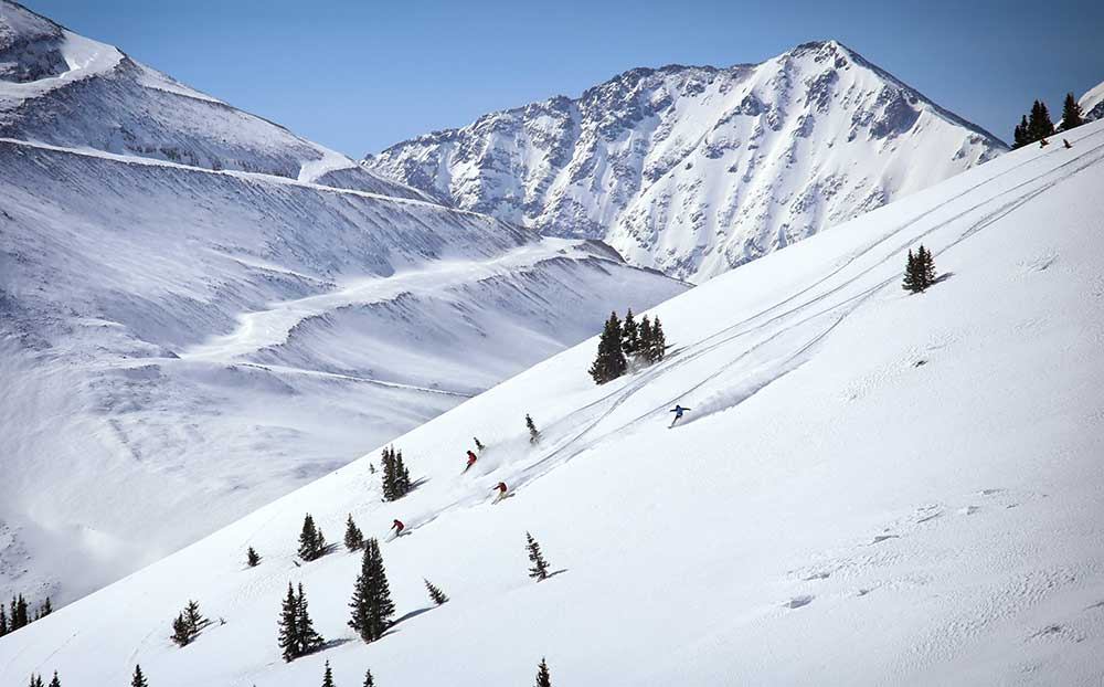 Skiers and snowboarders ride down Copper's Tucker Mountain terrain