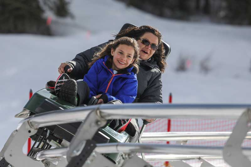 A woman and child come down the Rocky Mountain Coaster at Copper Mountain in Colorado
