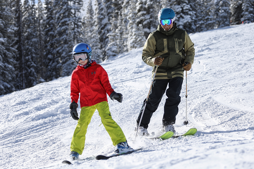 A father and son make their way down the mountain on skis at Copper Mountain Colorado