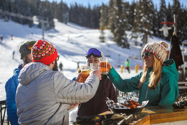 Group of skiers and riders cheersing for apres with drinks at Copper Mountain