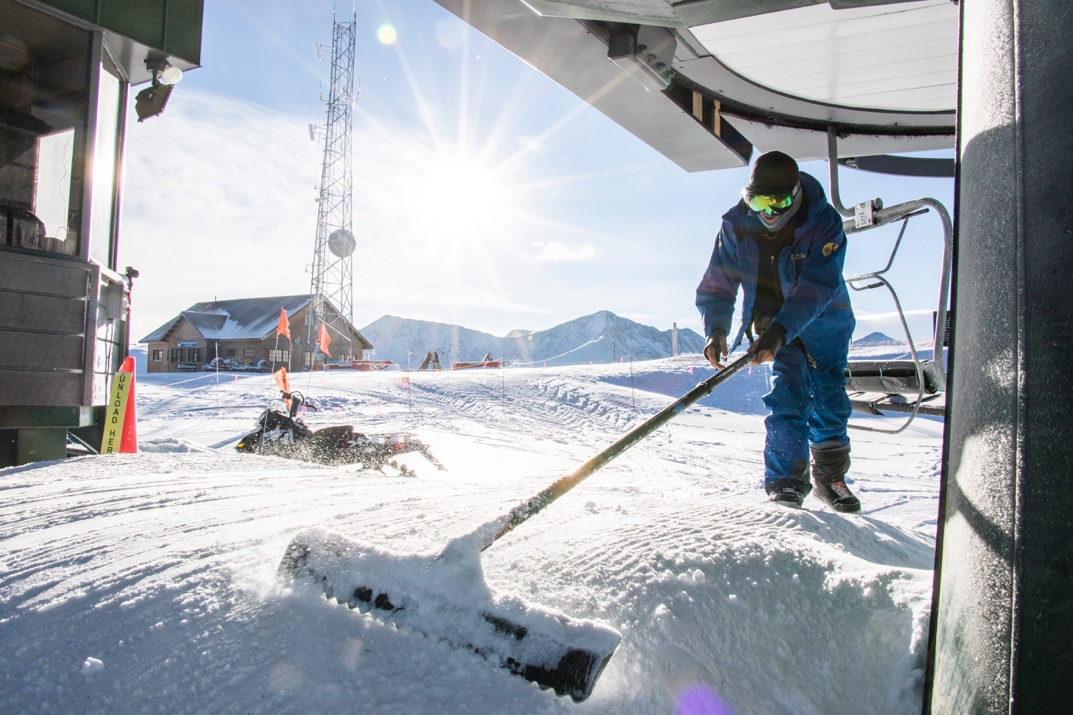 Lift operator Jake Mechem raking snow from top of Excelerator chairlift at Copper Mountain