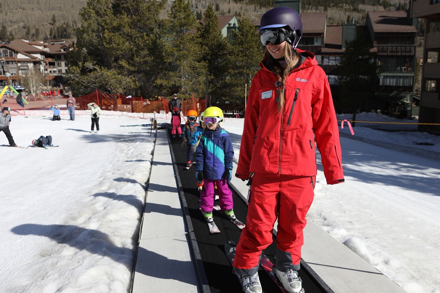 A Ski and Ride School instructor takes students up Easy Rider magic carpet at Copper Mountain
